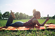 Woman with smartphone lying on blanket on a meadow - GIOF001156