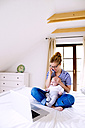 Mother with baby at home working with laptop - HAPF000456