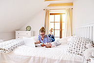 Mother with baby, cell phone and laptop on bed - HAPF000459