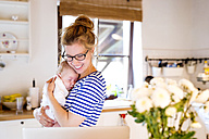 Happy mother with baby in kitchen looking at laptop - HAPF000468