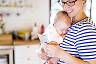 Mother holding little baby looking at cell phone - HAPF000471