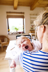 Mother at home holding crying baby - HAPF000474