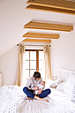 Father with baby sitting on bed - HAPF000483