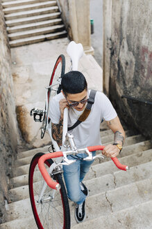 Young man carrying a bicycle on stairs - GIOF001167