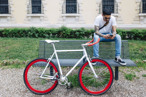 Young man with a bicycle sitting on bench - GIOF001170