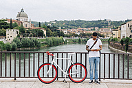 Italy, Verona, young man with a bicycle standing on a bridge - GIOF001179
