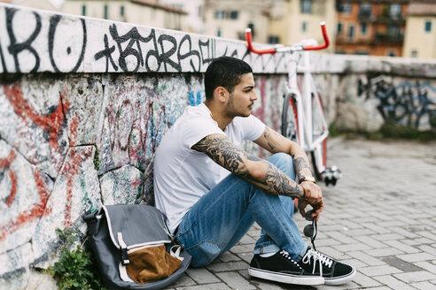 Young man sitting at graffiti wall - GIOF001182
