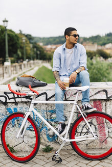 Young man with a bicycle sitting on graffiti wall - GIOF001185
