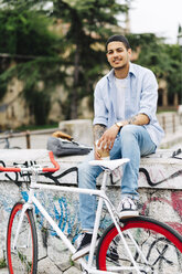 Smiling young man with a bicycle sitting on graffiti wall - GIOF001188