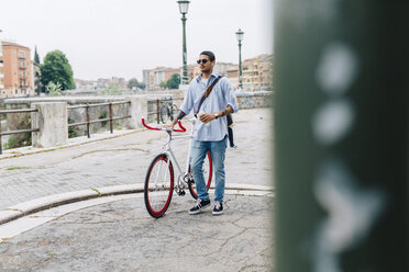 Young man walking with a bicycle in the city - GIOF001191