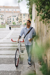 Young man walking with a bicycle in the city - GIOF001194