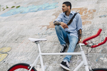 Young man with a bicycle sitting on a wall - GIOF001200