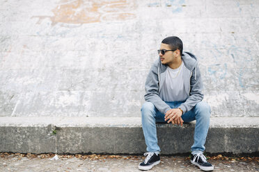 Young man sitting on a wall wearing a hoodie - GIOF001203