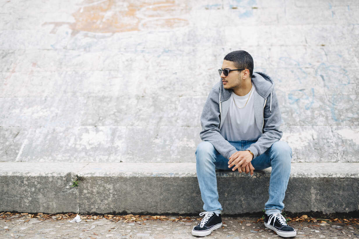 Young man sitting on a wall wearing a hoodie - GIOF001203 - Giorgio Fochesato/Westend61