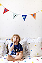 Portrait of little boy with lollipop sitting on the couch - MGOF001885