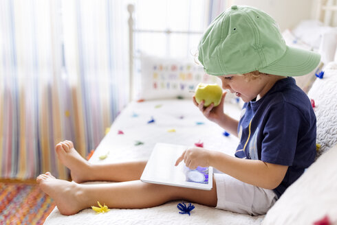 Little boy sitting on the couch with an apple using digital tablet - MGOF001891