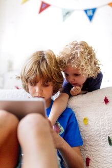 Two little brothers using tablet at home - MGOF001900