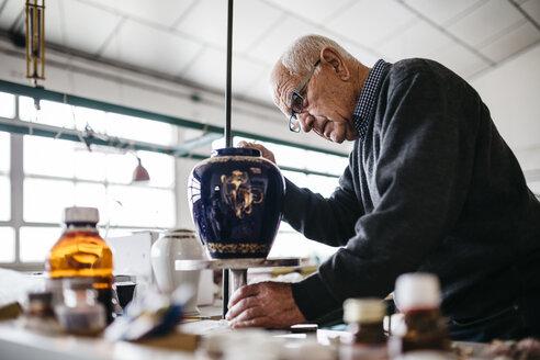 Senior man decorating ceramic vase in his spare time - JRFF000685