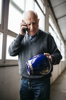 Elderly man reviewing the ceramic vase, talking on the phone - JRFF000694