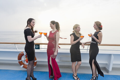 Four women with aperitives standing on deck of a cruise liner - ONBF000026
