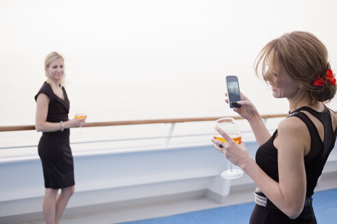 Laughing woman taking a picture of her friend on deck of a cruise liner - ONBF000029