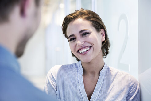 Portrait of smiling woman talking to a man - FMKF002615