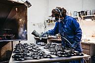 Female worker painting ceramics with spray gun - JRFF000705