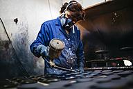 Female worker painting ceramics with spray gun - JRFF000708