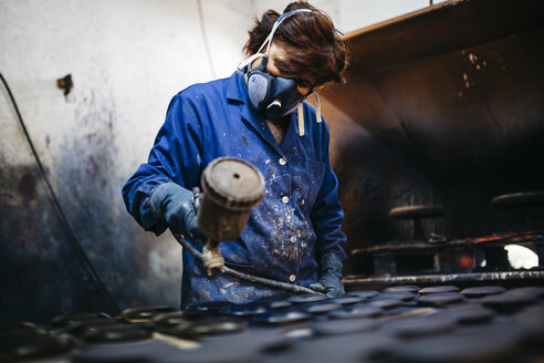 Female worker painting ceramics with spray gun - JRFF000708