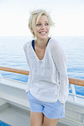 Portrait of blond woman standing at the railing of a cruise ship - ONBF000034