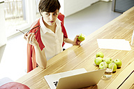 Woman in a modern canteen eating an apple - TSFF000024