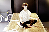 Woman practising yoga on wooden table - TSFF000027