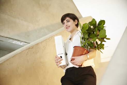 Woman with folder and potted plant standing on staircase - TSFF000033