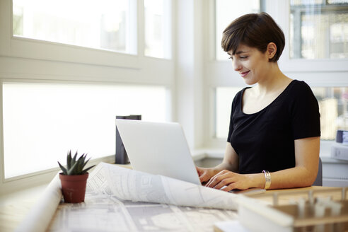 Portrait of young architect using laptop in her office - TSFF000039