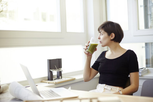 Portrait of woman drinking green smoothie in the office - TSFF000042