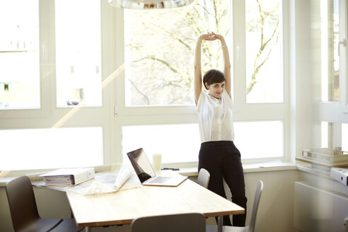 Woman doing stretching exercise in her office - TSFF000048