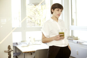 Daydreaming woman with glass of green smoothie in an office - TSFF000051