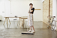 Smiling woman with broom in a studio - TSFF000063