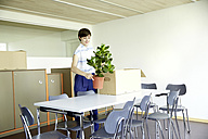 Woman with potted plant in new office - TSFF000078