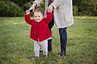 Smiling toddler holding her mother's hands in a park - LITF000367
