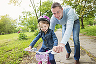 Father accompanying daughter on bike - HAPF000486