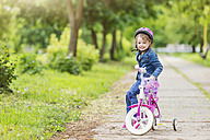 Smiling girl on bike with training wheels - HAPF000489
