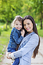 Portrait of mother holding daughter in park - HAPF000498