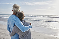 Back view of couple on the beach looking to the sea - RORF000213