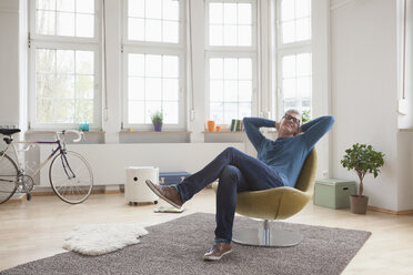 Relaxed mature man at home sitting in chair - RBF004536