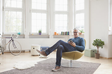 Mature man at home sitting in chair using digital tablet - RBF004539