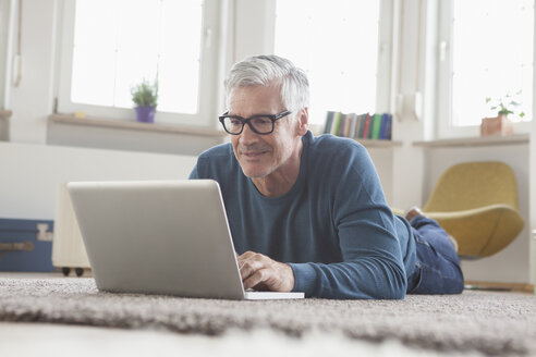 Mature man at home lying on floor using laptop - RBF004542