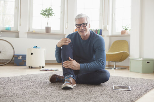 Relaxed mature man at home sitting on floor - RBF004545
