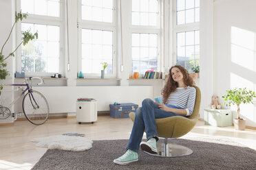 Relaxed woman at home sitting in chair - RBF004551