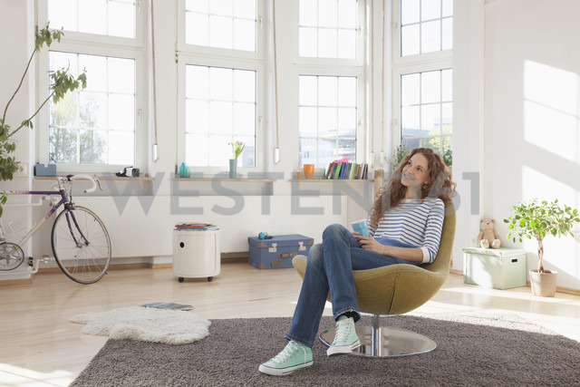 Relaxed woman at home sitting in chair - RBF004554 - Rainer Berg/Westend61